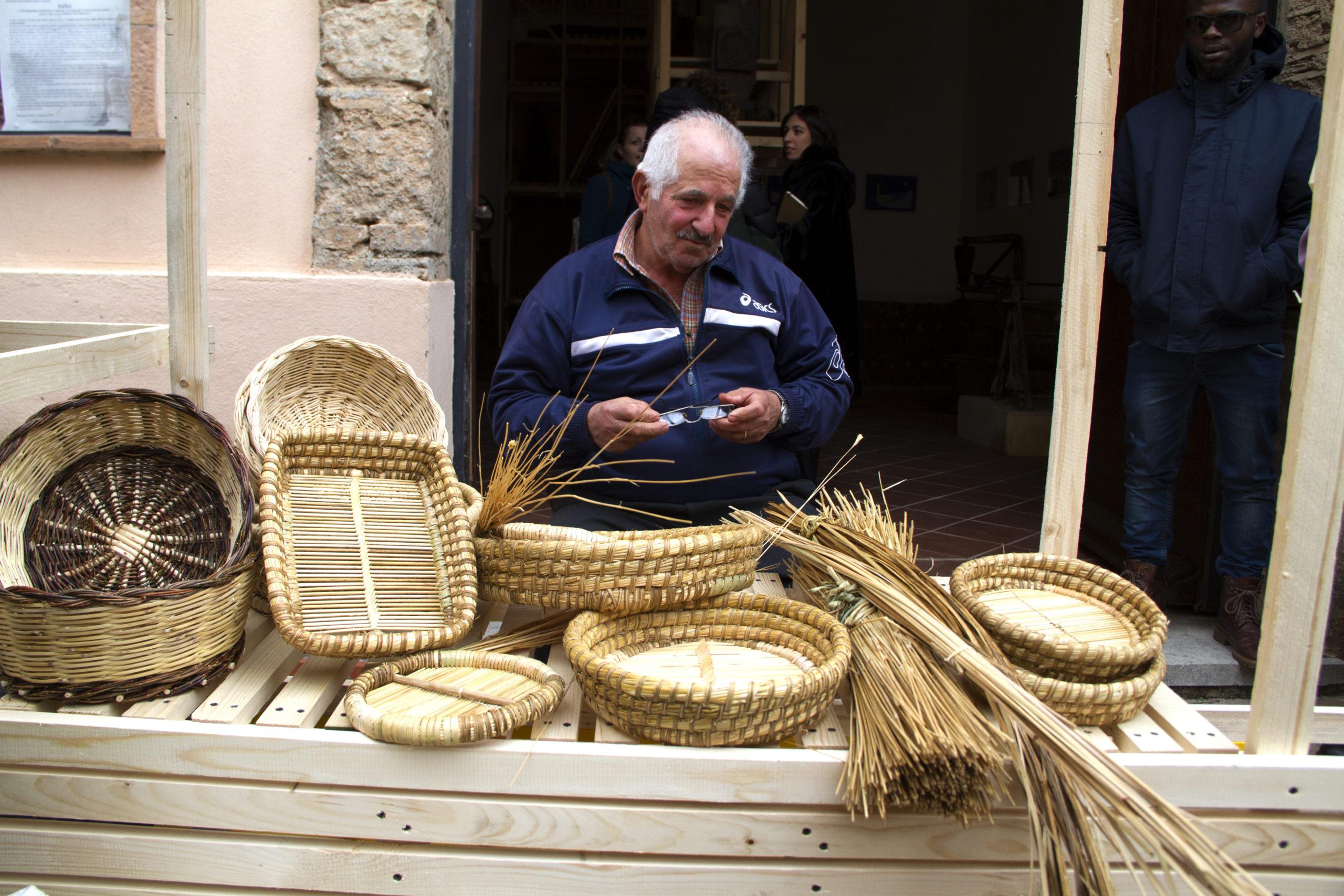 Artigiano locale presenta cestini di vimini